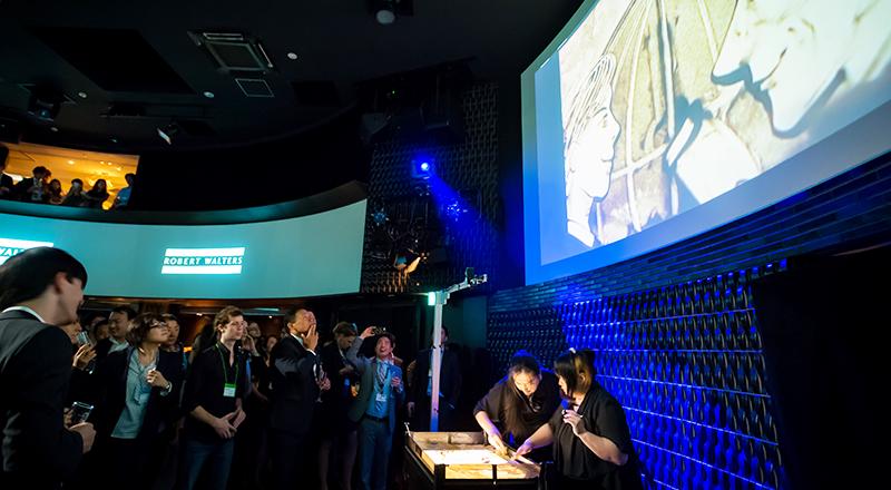 イベント会社のニューズベース|360°に張り巡らせたスクリーンを活用したサンドアートに見入る参加者